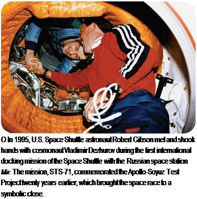 Подпись: О In 1995, U.S. Space Shuttle astronaut Robert Gibson met and shook hands with cosmonaut Vladimir Dezhurov during the first international docking mission of the Space Shuttle with the Russian space station Mir. The mission, STS-71, commemorated the Apollo-Soyuz Test Project twenty years earlier, which brought the space race to a symbolic close.