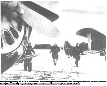 Подпись: Soviet p lots approaching their И 53s on an airfield near Murmansk during the winter of 1941-1942. One advantage the 1-153 had over most German and Soviet fighters was its ability to operate reliably unde' the most adverse weather cond tions. [Photo: Autho'S' collection.)