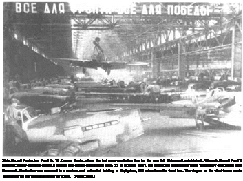 "Подпись: State Aircraft Production Plant Nc 18 Znamia Truda, where the first rrass-production line for the new II-2 Shturmovik established. Although Aircraft Plant '8 sustainec heavy damage during a raid by two expert crews from III./KG 55 in October 1941, the production installations were successful1/ evacuated from Voronezh. Production was resumed in a roofless and unheated building in Kuybyshev, 350 miles from the front line. The slogan on the steel frame reads: ""Everything for the front, everytning for victory."" (Photo: Seidl.)"